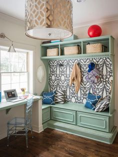 """Wallpaper from Schumacher delivers major personality. """"It would have looked too bulky if all you saw was woodwork,"""" Laura says. With coat hooks, baskets, and smart drawers for charging electronics, the custom built-in encourages tidiness."""