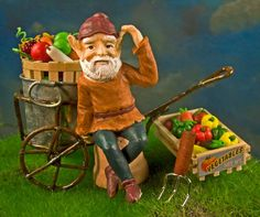 A miniature garden gnome shows off his miniature garden harvest.