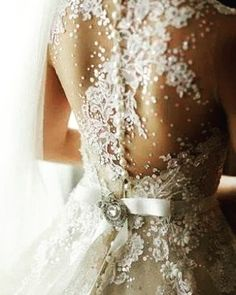 I'm obsessed with lace! I love the  way it looks on this dress like it's been pasted on this bride's skin. Brooch lace ribbon those cute round butttons couture... what more could one ask for in a wedding dress?   Wish I could wear something like this on my wedding day.   #weddingdress #lacedress #weddinginspo #weddinginspo #weddingwishlist #Couture #Blogger #Wedding #Bridetobe  #DressDesign