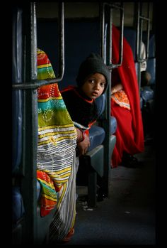 train ride, india. Love the colors captured I'm this photo. And this little boys expression.