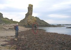 Witness Statement: My son took this photo of me at the Rock and Spindle on the coast east of St Andrews. Right in the centre of the image is a person standing in the water in wellingtons facing to the right and wearing an anorack with the hood up. It WAS a chilly day. We were definitely alone at the time and it really spooked us when we looked through the pictures once home and saw this.