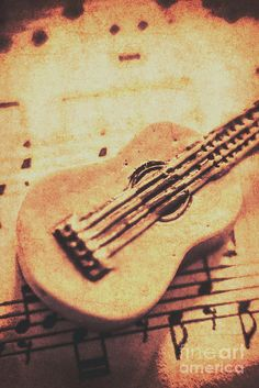 Sepia toned weathered close up on single little carved guitar on sheet music. Folk songs by Jorgo Photography - Wall Art Gallery