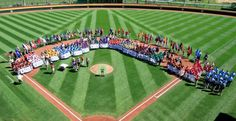 The 16 Little League baseball teams competing in the 2013 Little League World Series line the infield of Volunteer Field for the opening ceremony  in South Williamsport, Pa. Thursday. (Gene J. Puskar/AP)