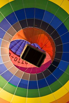 A view from the ground of a hot air balloon passing overhead.