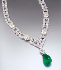 Art deco emerald and diamond necklace by Chaumet. Designed as graduated openwork rectangular links with two-stone spacers set with four cushion-shaped diamond collets, the central openwork plaque suspending a circular-cut diamond and drop-shaped emerald pendant (may be worn as a bracelet) circa 1930, necklace 39.0 cm long, bracelet 19.0 cm long, with French assay marks for platinum and gold, in an original Chaumet blue leather fitted case.