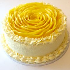 Mango mousse cake with whipped cream and decorated with mango rosette.