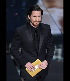 Christian Bale wore a Gucci black peak lapel Signoria tuxedo w/ black dress shirt and slim black satin tie at 84th Annual Academy Awards - Feb 26, 2012