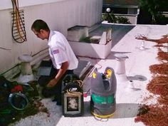 An All Weather Heating & Air Conditioning technician installs a furnace unit on a client's roof.