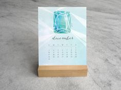 """This 12-month desk calendar features original illustrations of each month's birthstone. Printed on a sturdy 4.25"""" x 5.5"""" card. The cards sit in a finely-crafted"""