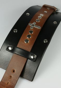 "3"" wide leather cuff made to resemble the same cuff worn by fictional character Merle Dixon. - The cross is 1"" long. - Solid brass buckle closure. - Brass rivets, nickel and chrome polish."
