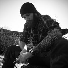 The weather is all black and white. Better put a pointy end to this stick! Knitted hat, tattoos, plaided shirt and black beard.