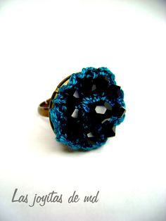 Anillo de croché. Roseta en color azul turquesa decorada con piedras de swarovski negras.