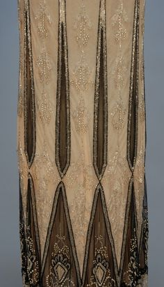 JEWELED FLAPPER DRESS, 1920's. Sleeveless white and black net over nude chiffon, pieced in an arrow and diamond pattern, decorated with crystal and black beads and rhinestones, scalloped hem with beaded rings. Detail