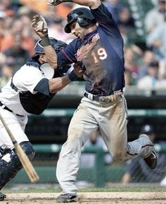 Detroit Tigers catcher Gerald Laird, left, tags out Minnesota Twins' Darin Mastroianni (19) who was trying to steal home in the seventh inning of a baseball game on Thursday, July 5, 2012, in Detroit. The Tigers defeated the Twins 7-3