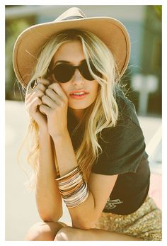 Large hat, stacked bangles, sequin shorts, sunglasses and dark top.