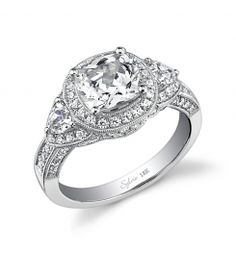 Style SY447S  2-Carat Cushion Cut Diamond Engagement Ring    This magnificent platinum three-stone engagement ring features a 2-carat cushion-cut center diamond. Accompanying the center are two 0.2-carat round brilliant side diamonds and round diamonds surrounding the center stones and streaming down the sides for a total weight of 1.08 carats.