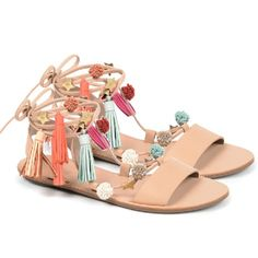 Flat leather sandals with tassels and pom poms.