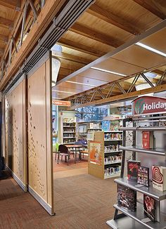 I like the moving panels. cei  A factory-constructed modular system forms the new Fife Library, Pierce County Library System, WA. Digitally fabricated, track-based divider panels bearing a custom pattern separate the library spaces from community areas available for public functions. CREDITS: SHKS Architects, architect; photo, ©2011 Benjamin Benschneider.