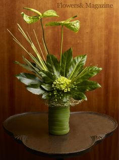 Wavy green anthuriums shelter the base of the monochromatic arrangement while hydrangea, hypericum and green midollino reinforce the radial lines of the fatsia foliage. #flowersand #flowers #floraldesign