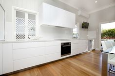 Kitchen Renovations | Makings of Fine Kitchens Brisbane - love these pull out cupboards no handles - white looks great against timber flooring - oven and dishwasher don't look quite right though