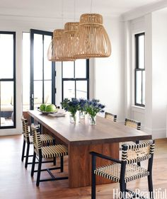 Black window mullions and door and chair frames add graphic punch in a family vacation home on Sullivan's Island, South Carolina. For beachy boldness, designer Sally Markham lit the dining table with rattan Orbita pendant lamps by Tomoko Mizu. Gervasoni's Otto dining chairs are woven rawhide on ebonized wood.