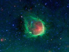 Green Ring Nebula as seen by NASA's Spitzer Space Infra Red Telescope:   The green ring is where dust is being hit by winds and intense light from the massive stars. The green color represents infrared light coming from tiny dust grains called polycyclic aromatic hydrocarbons. These small grains have been destroyed inside the bubble. The red color inside the ring shows slightly larger, hotter dust grains, heated by the massive stars. #Astronomy #Spitzer_Telescope #Green_Nebulae