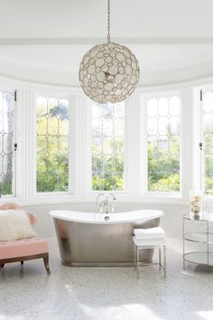 The wife's bath is filled with feminine touches, including a crystal-and-capiz-shell pendant light from HD Buttercup and a slipper chair by Grace Home. An RH stool sits beside a Signature Hardware tub. Family Room, Home And Family, Grace Home, Exclusive Homes, Tufted Chair, Mediterranean Style Homes, Leaded Glass, Architectural Digest, Architectural Features