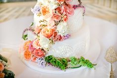 simple white frosting designs with flower decorations on top. love the mix.