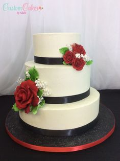 Classic wedding cake with red sugar roses and black ribbon