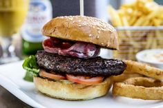 British beef burger in a seeded brioche bun with bacon, onion rings, salad garnish, relish & fries. Riverside Garden, Onion Rings, Hotel Spa, Lake District, Fries, Brioche Bun, Bacon, Lunch, Seeded