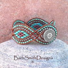 The Twisted Sister in Turquoise  Shes the most desired girl in the bunch! What makes this sister twisted is the leather weaves that give this cuff her shape! This unique 5-row cuff bracelet features curves of Nickel Plate and Opaque Picasso Turquoise and Coral Red beads, surrounded by coordinating seed beads. It is hand-stitched on Distressed Light Brown Indian Leather Cord and fastens with a 5/8 silver Bali button surrounded by a double beaded button loop.  Finished Size: 6 3/4 Fit...