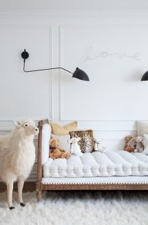 Rich, white nursery. Love the sconces and the day bed.