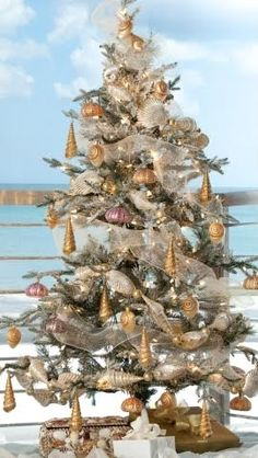 A Snow Dusted Coastal Christmas Tree with Golden Blown Glass Shell Ornaments by RSH.