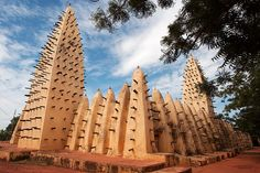 The Bobo Dioulasso Grand Mosque in Burkina Faso is a century old West African mosque, with timbers sticking out, similar in style to Djinguereber Mosque in Timbuktu. The timbers are in place allowing workers to scale the structure for adding extra layers of clay, as clay and timbers are the only materials from which this building is made.