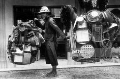 A man selling hardware from the baskets on his shoulders on the street in Bangkok.