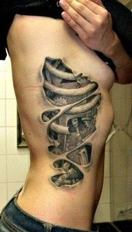 Side tattoo of shredding skin, exposing the ribs and mechanical/mechanoid body parts. Tonal black and grey. Very cool art!