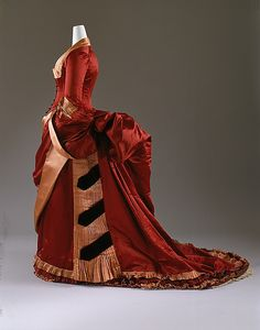 """Evening dress, American or European, ca. 1884-86. Silk. Met: """"The bustle was at its greatest extension by 1885. It was almost perpendicular to the back and heavily upholstered. The 1880s versions were as padded and heavily embellished as a drawing-room hassock of the period."""""""