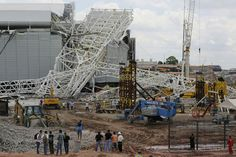People stand in front of a metal structure that buckled on part of the Itaquerao Stadium in Sao Paulo, Brazil. Part of the stadium that will...
