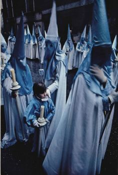 A penitent encourages his son as he prepares for his initial procession with a religious brotherhood during Holy Week in Valladolid. Spain, March 1978