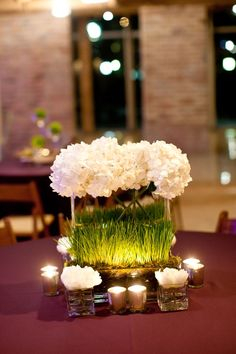 I like the square vases & grass used here, along with the lights. (Modern White Hydrangea Centerpiece)