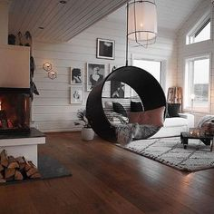 Here we have the wood on the floor, on the walls and ceiling. Floor in color of wood makes the room a great place to live. Pictures take care to kill the monotony of pure white walls and ceiling. And there's the inevitable fireplace that warms the soul and the room.