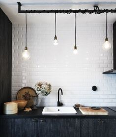 Have an obtrusive plumbing pipe you can't relocate? Work with it! Hanging these beautiful lightbulbs over the workspace (in this instance the sink) is really genius!