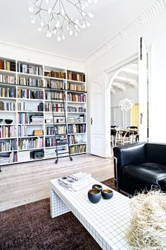 Scandinavian home with a floor to ceiling library. We love the rolling library…