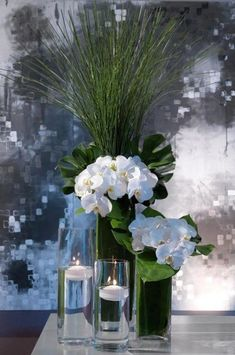 Picture of a tropical beach wedding centerpiece with tall glasses with floating candles, white orchids and monstera leaves plus grasses Beach Wedding Centerpieces, Floral Centerpieces, Centerpiece Ideas, Wedding Beach, Chic Wedding, Trendy Wedding, White Orchid Centerpiece, Vase Arrangements, Wedding Ideas