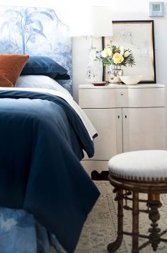 The graphic but subtle fabric on the blue headboard makes a statement without overhwhelming. - Traditional Home ®/ Photo: John Bessler / Design: Lisa Sternfeld