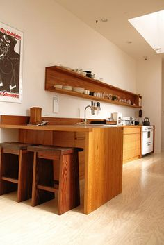 "I love this ""modern but organic"" look.  Love the open shelving with closed back.  Cookbooks at the far end?"
