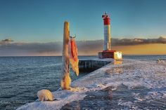 Icy Oakville lighthouse pier in the winter at sunset.