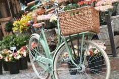 Bicicleta verde pastel con cesto.