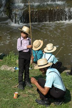 An Amish father helps his son bait a hook during a fishing derby in Lancaster County.