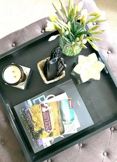 Overhead shot of an ottoman tray that;s styled for Spring. Tips and tricks and inspiration for styling a tray for a coffee table/footstool or ottoman in your living room